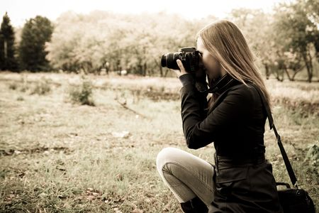 outside shooting: woman the photographer on the nature