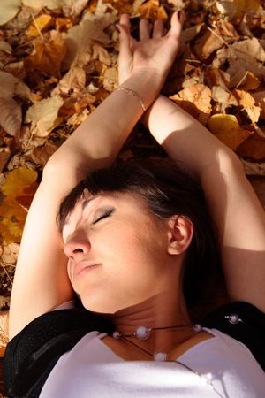 lays: beautiful young woman lays on autumn leaves