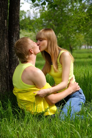young guy and the girl kiss in park