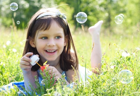blowing bubbles: little beautiful happy girl blowing soap bubbles  Stock Photo