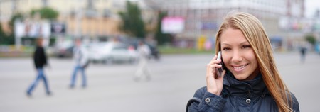 happy young woman speaks by phone on the street photo