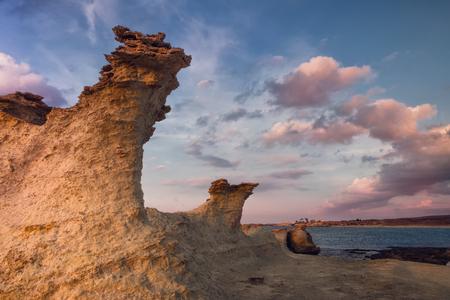Beatiful Cyprus sunset on the desert empty rocky coast with strange fiqures at the Halk beach Stok Fotoğraf