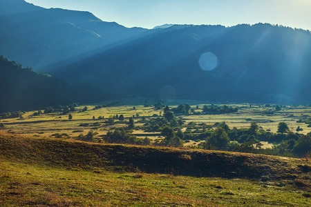 Morning landscape with blue mountains and green valley with lense flare