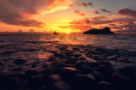 Sea landscape with dramatic sunset and ship on horizon