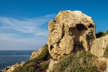 Huge rock strange form with holes. The desert landscape with prickly bush, sea and blue sky. 写真素材