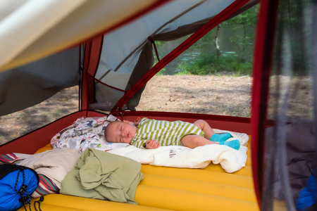 Little boy is sleeping on his back in green striped clothing inside a tent not far from summer lake