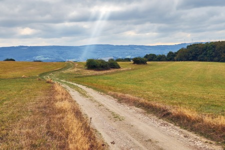 Rural ladscape with road going through a field and ray of light on a cloudy sky Stock fotó