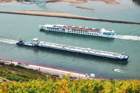 Long barge and motor ship swimming towards each other on the river Rhine in Germany