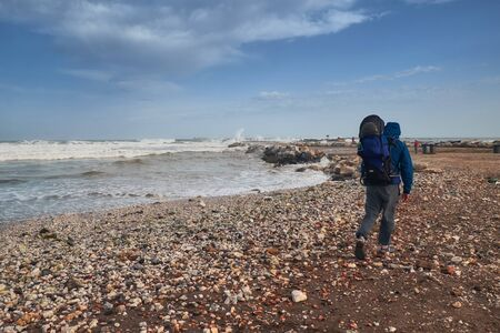 Father walking with his child in a backpack-carrying along the coastline in Malaga by the stormy sea