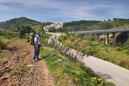 On the way to the Malaga city in full lightweight equipment in front of the highway over the bridge. Andalusia. Spain