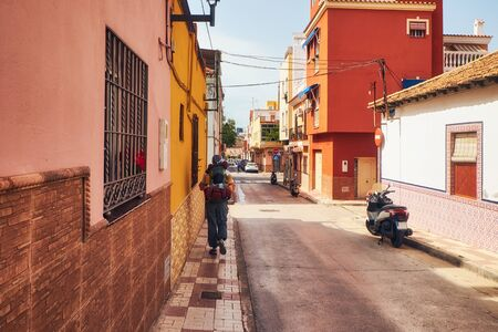Sunny street on the outskirts of Malaga and tourist walking away with backpack. Andalusia. Spain Stock fotó