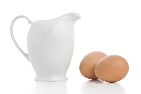 Porcelain Milk Jug With Two Eggs Isolated photo