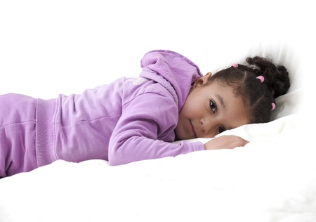 quiet baby: Cute Little Girl Lying in White Bed Stock Photo