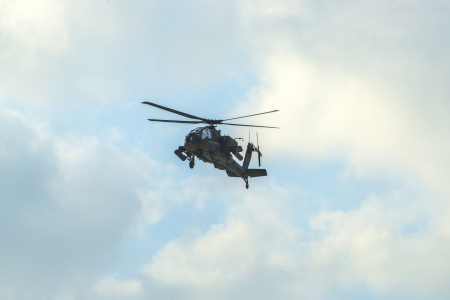 air demonstration: An Apache Helicopter Flying Over Blue Sky