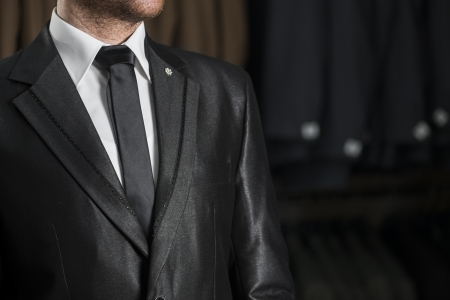 buttoning: Young Male in a Black Wedding Suit and Tie over White Shirt