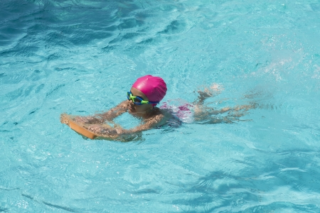 Little Young Girl Swimming in Blue Water of the Swimming Pool photo
