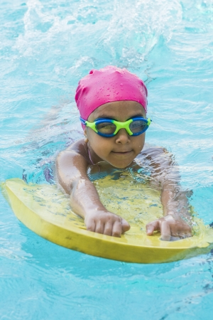Little Young Girl Learning Swimming in Blue Water of the Swimming Pool