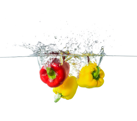 Red and Yellow Paprika Splash in Water Isolated on White Background
