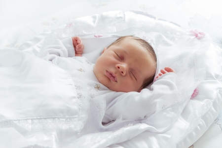 Little Newborn Sleeping over His White Bed