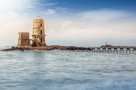 Old Ruined Lighthouse By Seaside at Sunset photo