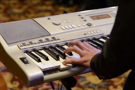 Close up of a pianist playing at the keyboard of a piano photo