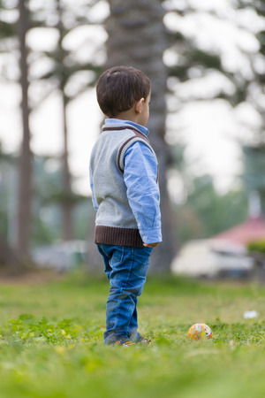 distant: A Little Boy Looking Away Standing on Green Grass Stock Photo