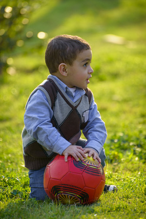 A Little Kid with A Ball over Green Grass photo