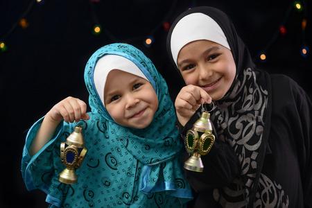 Happy Muslim Girls with Ramadan Lantern on Defocused Night Lights Background Foto de archivo