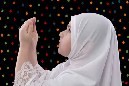 Young Muslim Girl Prayer on Defocused Night Lights Background photo