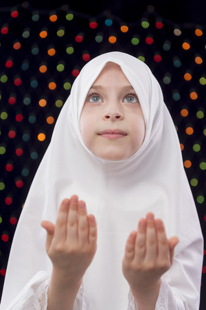 Muslim Girl Praying on Defocused Night Lights Background photo