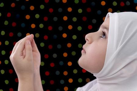 muslim prayer: Little Muslim Girl Prayer on Defocused Night Lights Background Stock Photo