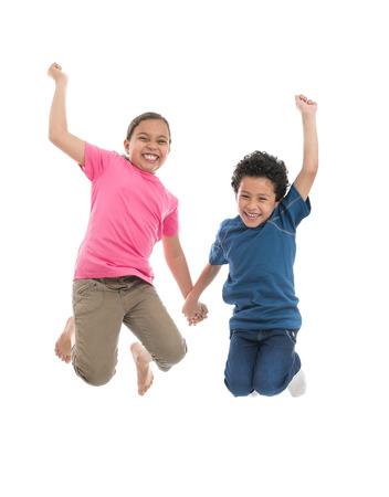 Niños alegres activa que salta con la alegría aislada en el fondo blanco Foto de archivo
