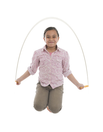 Young Girl Jumping with Skipping Rope Isolated on White Background Foto de archivo