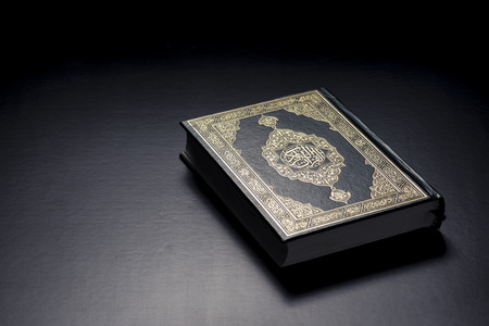 Islamic Holy Book Quran Under Soft Light on Black Background Stock Photo