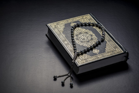 Islamic Book Holy Quran and Beads on Black Background