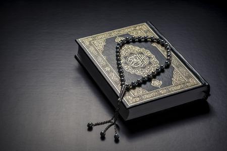 Islamitische Boek Heilige Koran en kralen op zwarte achtergrond