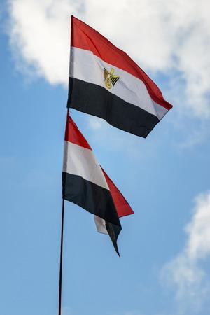 egypt revolution: Dual Egypt Flags Raised over Blue Sky Stock Photo