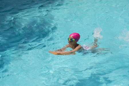Little Young Girl Swimming in Blue Water of a Swimming Pool photo