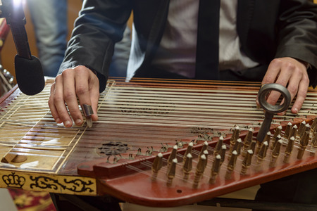 Male Hands Playing Arabian Qanon Musical Instrument During a Symphony photo