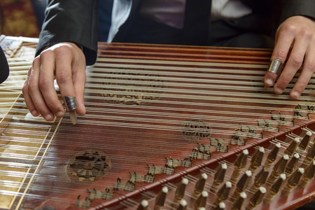 instrumentalist: Fingers Playing Arabian Qanon Musical Instrument During a Symphony Stock Photo