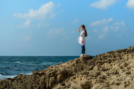 far away look: Young Beauty Girl By Sea Coast Under Sunlight