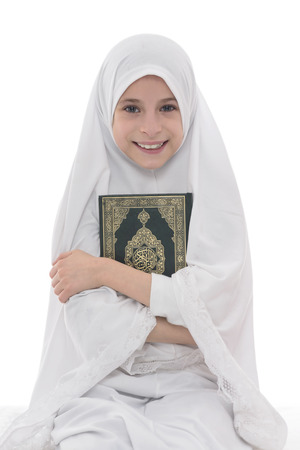 Smiling Muslim Girl Loves Holy Book of Quran Isolated on White Background Foto de archivo