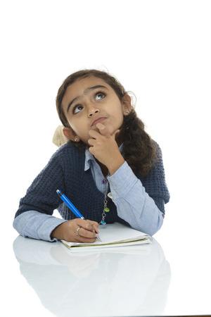 niños escribiendo: Colegiala joven de pensamiento por respuesta aislada sobre fondo blanco