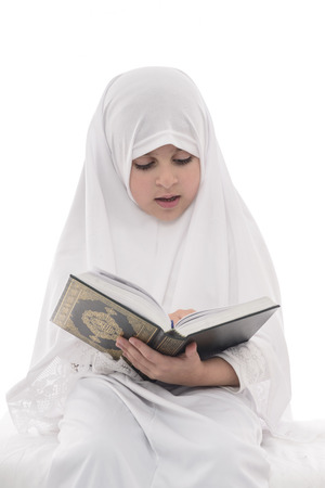 quran: Little Young Muslim Girl Reading Quran Isolated on White Background Stock Photo