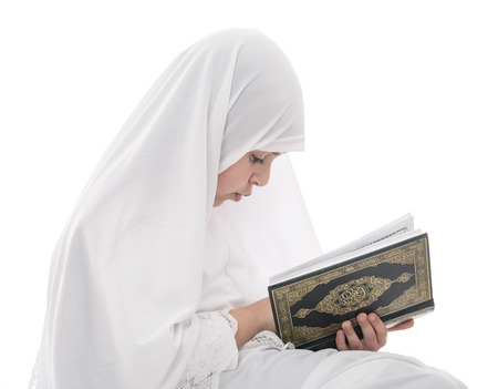 religions: Little Young Muslim Girl Reading Quran Holy Book Isolated on White Background Stock Photo
