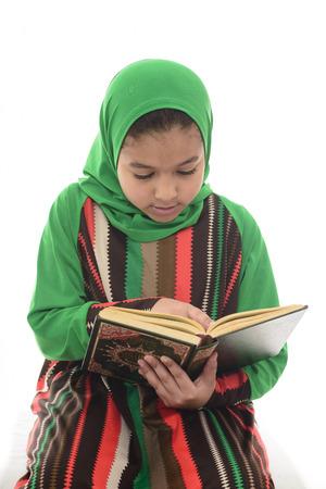 petite fille musulmane: Peu jeune musulmane Fille livre de lecture de Coran isolé sur fond blanc Banque d'images