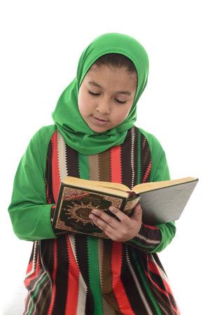 petite fille musulmane: Peu jeune musulmane Girl Reading Coran isolé sur fond blanc Banque d'images