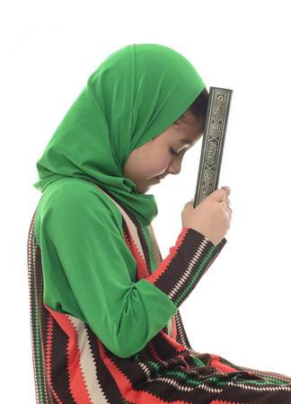 petite fille musulmane: Petite Jeune Fille tenant la musulmane Coran isolé sur fond blanc Banque d'images