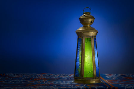 Dark Room With Ramadan Lantern over Ramadan Fabric Stock Photo
