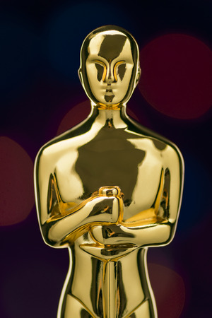 oscar: Closeup of Shiney Golden Statuette on Defocused Lights Background Stock Photo